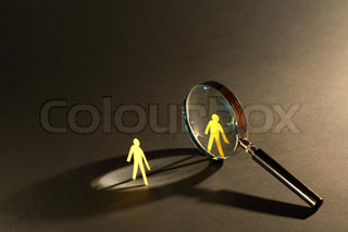 Magnifying glass standing between two small paper men on dark surface