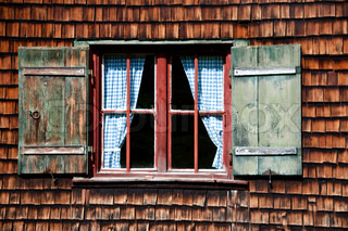 Beautiful ancient window on log house with wooden wall and blue curtains