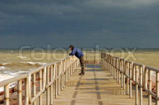 Lonely man standing on the pier