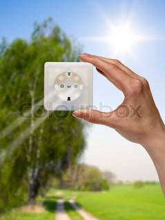 symbolic solar energy theme showing a idyllic outdoor scenery with human hand holding a electrical socket in front of the sun while sunbeams falling through