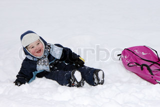 Smiling baby in winter with bobsleigh.