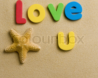 Letters spelling i love u in sand