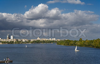 Sailing boat on the river with sityscape on background