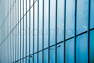Fragment of a modern glass building in blue tone