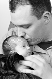 A newborn baby girl being by her dad as he kisses her head in black and white