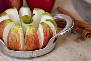 An apple is sliced into wedges and cored using a handy kitchen tool