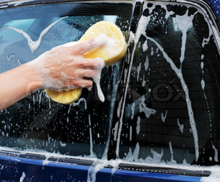 Man washing a car with a yellow sponge