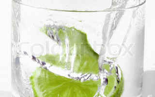Green alcohol cocktail with splash and green lime