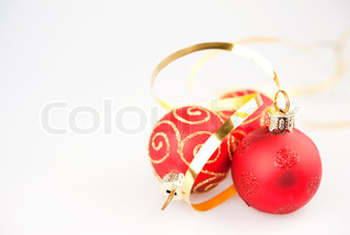 Three red Christmas ball ornaments with gold and with a gold ribbon on white background