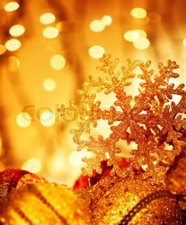 Golden Christmas tree ornament and holiday decoration with snowflake & blur lights