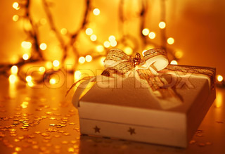 Gold holiday background with white present gift box, Christmas ornament and new year decoration over defocused lights