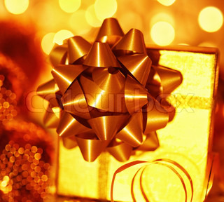 Golden holiday background with present gift box, Christmas ornament and new year decoration