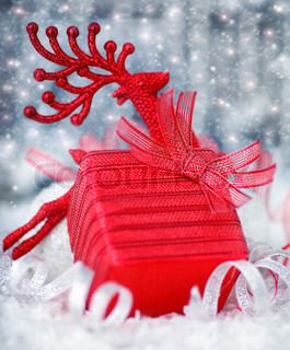 Christmas red gift box present as holiday background card with Christmas tree deer ornament & defocus lights decoration