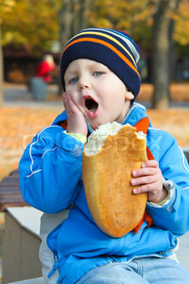Baby with one hand holding his cheek in his other hand holds the bread Walk in the autumn park