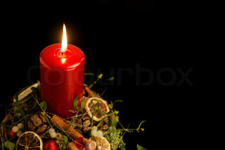 burning red christmas candle upon some decoration in front of black back