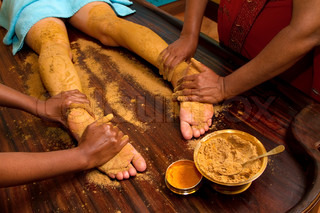 indian doctors doing traditional ayurvedic oil foot massage