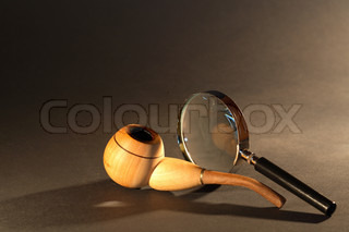 Old detective concept Magnifying glass and tobacco pipe on dark surface