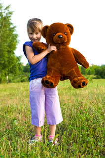 happy girl with brown teddy bear playing in a meadow best friends