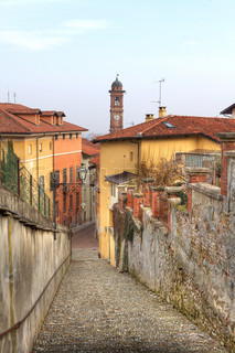Vertical oriented image of narrow street among walls and multicolored houses in Saluzzo, northern Italy