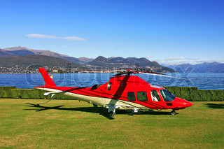 Red helicopter on the landing field in the background of Lake Maggiore in Northern Italy