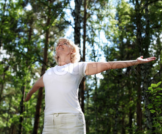 Elderly woman playing sports in the forest