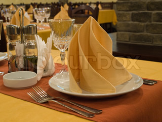 dinner table with yellowplacemats and napkins