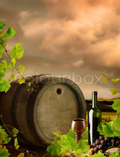 Red wine with grapes, grapevine and old cask in sunset landscape