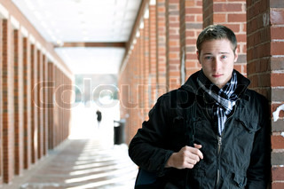 A portrait of a young man standing in an outdoor corridor with his backpack