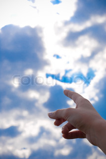 finger pointing at the blue sky with clouds