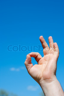 hand show ok sigh against the blue sky