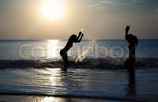 Silhouettes of two girls playing with water at summer beach during sunset