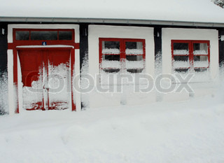 A Snow Covered House with Red Window Panes