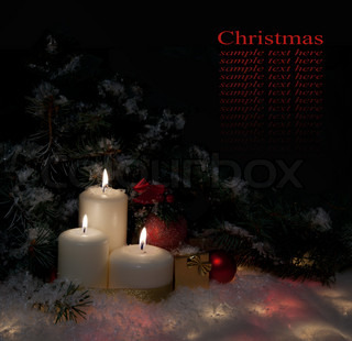 Christmas gift boxes with burn candles under decorated fir on snow