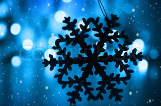 Blue snowy Christmas holiday background with tree decoration snowflake ornament and bokeh lights