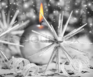 Silver holiday background with candle and Christmas tree ornament and decoration