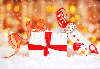 Holiday background with cute snowman Christmas tree decorative ornament & gift box in snow over abstract defocus lights