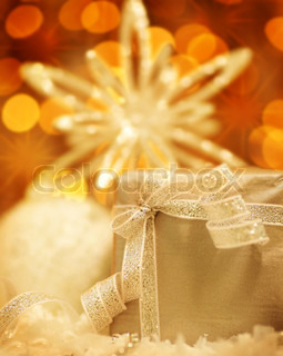 Winter holiday background with silver present gift box, star ornament & Christmas lights decoration