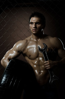 the very muscular handsome sexy guy with rubber-tire andwrench bearing,onnettingsteel fence background