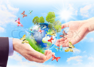 The earth in human hands, grass, trees and butterflies Concept of heritage earth for future generations