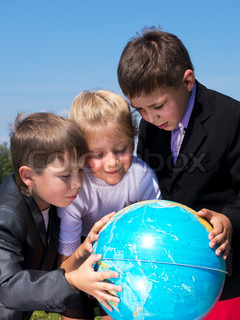 three kids holding earth globe over blue sky background