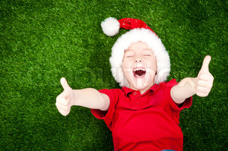 cute boy in santa hat on the green grass with thumbs up