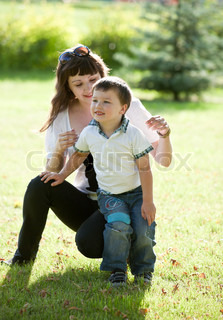 Young mother with son having fun on green grass