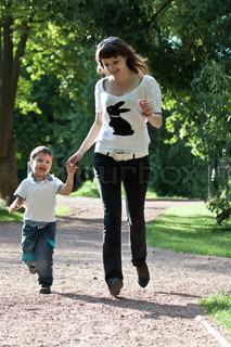 Young mother with son having fun in park, at summer