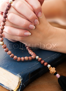 close up shot of female hands praying with rosary on vintage blue holy bible