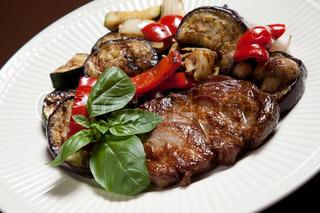 Steak mit gegrilltem Gemüse und Pilze auf einem weißen Teller mit Basilikum dekoriert