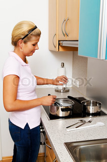 a woman in the kitchen while cooking with electric stove