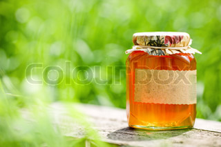 Honey jar on table against nature background