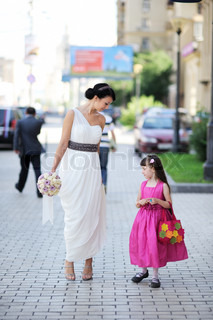 Beautiful bride posing together with flowergirl princess