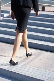 Businesswoman walking up stairs on stairway, low section