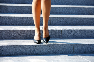 Woman stepping down on stairway in city